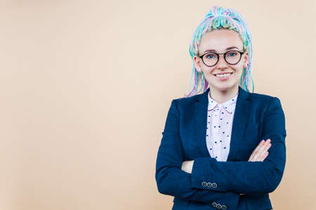 Positive modern business lady with colored dreadlocks is smiling. Young woman, leader, trainer, speaker, coach in suit glasses is looking confidently.  Entrepreneur, director, head of company concept. Imagens