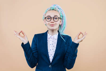 Business lady with colored dreadlocks is meditating, relaxing. Young woman girl in suit, glasses keep calm looking for harmony. Stress at job concept. Director is practicing yoga to solve problem Imagens