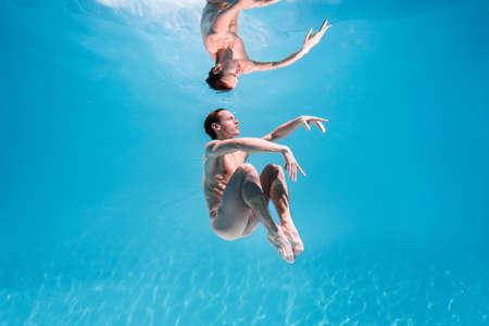 Male Caucasian man swimmer diver dancer swims under water in the sea. Summer tourism, travel journey trip voyage, holiday and vacation. Concertation, art, beauty and freedom concept
