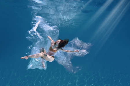 Fashionable and athletic girl free diver alone in the depths of the ocean. Swimmer brunette diving deep in ocean on blue underwater background. Pollution, plastic and ecology concept