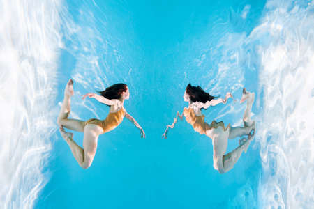 Fashionable and athletic girl free diver alone in the depths of the ocean. Swimmer brunette diving deep in ocean on blue underwater background. Concentration, freedom and beauty concept