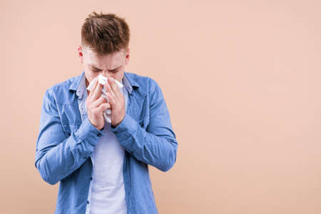 Allergy concept. Home treatment. Young sick man has runny nose. Flu and virus infection, coronavirus covid-19 symptoms. Immunity against epidemic, pandemic. Hipster blow out snot, sneezing in paper. Stock Photo