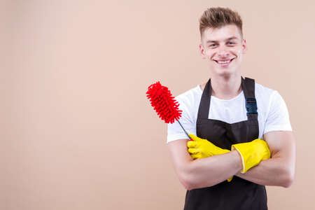 Happy young man, cleaning guy in uniform yellow latex gloves is smiling while standing against beige background. Clean with fun concept. Playful househusband is holding red microfiber duster.