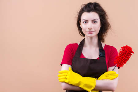 Happy young woman, cleaning lady in uniform yellow latex gloves is smiling while standing against beige background. Clean with fun concept. Playful housekeeper is holding red microfiber duster. Stock Photo