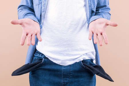 Closeup man is holding his turning out empty pants jeans pocket to show no cash inside isolated on beige background. Unemployed male spent money. Financial crisis, problems, bankruptcy, poverty.