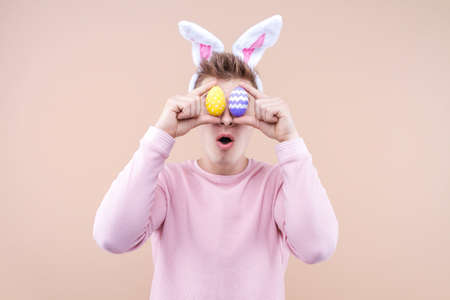 Studio portrait of surprised young funny man wearing traditional rabbit bunny ears headband for celebrating. Shocked male is holding eggs over beige background. Happy Easter and spring concept.