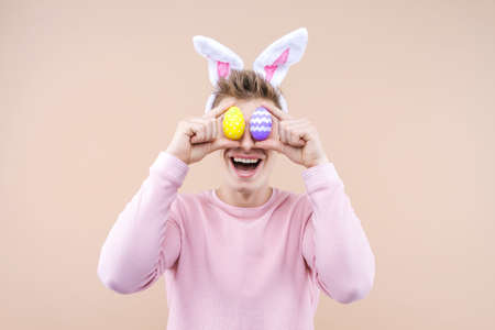 Studio portrait of smiling young funny man wearing traditional rabbit bunny ears headband for celebrating. Playful male is holding eggs over beige background. Happy Easter and spring concept.
