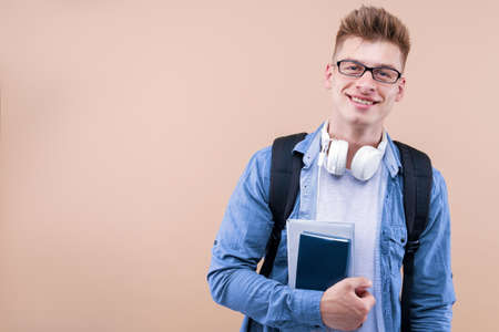 Portrait of smiling student man in spectacles is holding books, copybooks, isolated on beige background. Positive guy in denim shirt and backpack is ready to lesson lecture. Back to school concept.
