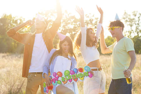 Happy excited friends having fun outdoor celebrating. Young millenial people enjoying summertime together at garden party - Cheerful friendship concept. Birthday Party festival concept.