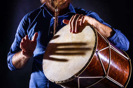 Closeup male hands are drumming on ethnic rhythm percussion musical instrument jembe. Drummer is playing african indian music. Traditional tribal culture performance. Summer festival concept.