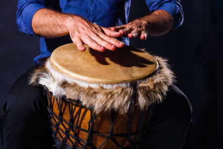 Percussion musical instruments and culture concept. Closeup male musicians hands are playing with turkish darbuka, african indian jembe drum. Summer festival concert performance. Ethnic rhythm.