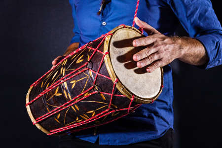 Closeup drummer male hands with jembe. Man is drumming on wooden ethnic drum. Percussion musical instrument. Musician is playing live ethno rhytm music. Summer festival concept. Modern art hobby. 스톡 콘텐츠