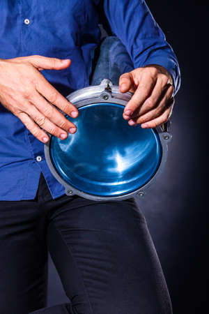 Closeup drummer male hands with drum. Man is drumming on metallic blue percussion musical instrument. Musician is playing live ethno rhytm music. Summer festival performance concept. Modern art.