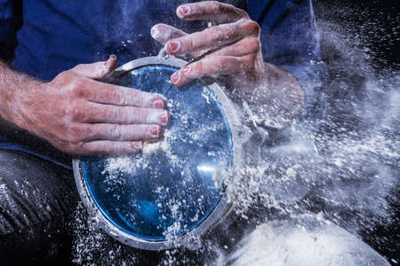 Man is playing on djembe drum, covered with talcum powder. Flour splashes on dark background. Summer festival concert performance. Ethnic rhythm. Percussion musical instruments and culture concept. 스톡 콘텐츠