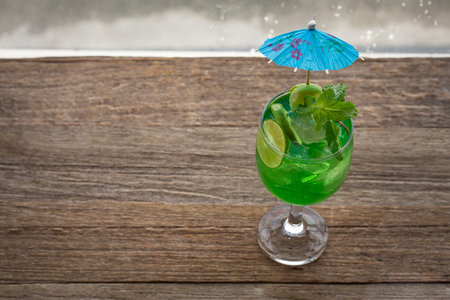 cocktail strainer: margarita cocktail with salty rim on wooden table with limes and mint