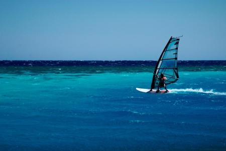 windsurfer rushing along bright blue lagoon