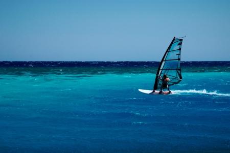 windsurfer rushing along bright blue lagoon