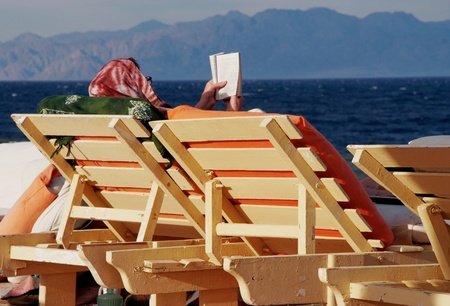 women sitting on beach chair and reading  Stock Photo