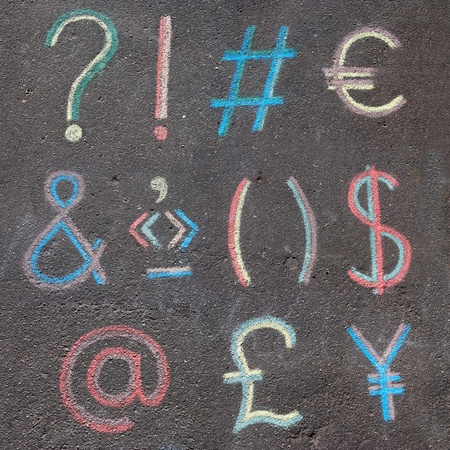 punctuation marks, mathematical symbols and currency symbols drawn on asphalt with chalk photo