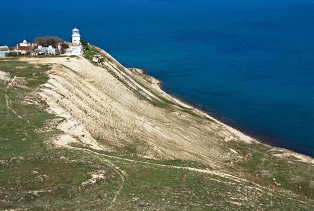Old white lighthouse on sea coast photo