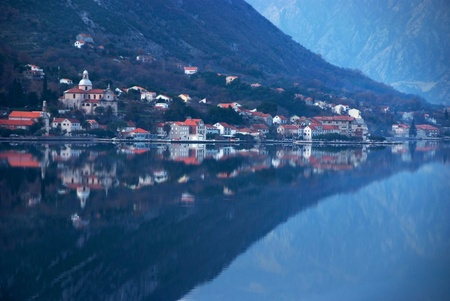 waterscape with old town against the mountain and perfect  mirror image photo