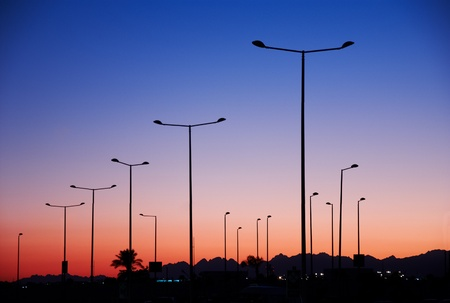 pillar street spotlights in front of sunset sky photo