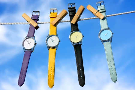 composition of colourful watches on blue sky background photo