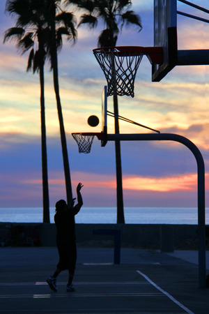 basketball player in front of sunset over Venice Beach in LA, California