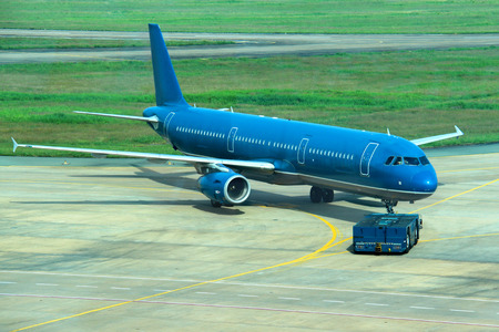 Blue commercial airplane taken in tow photo