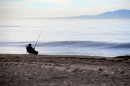 relaxed fisherman fishing on the ocean beach photo