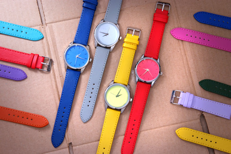 set of colorful watches on cardboard background