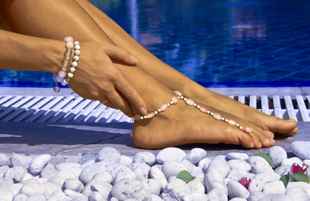 Woman posing by the pool with bracelets Stock Photo