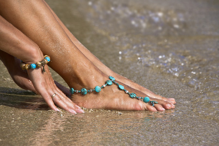 Woman posing on wet sand with summer styles bracelets