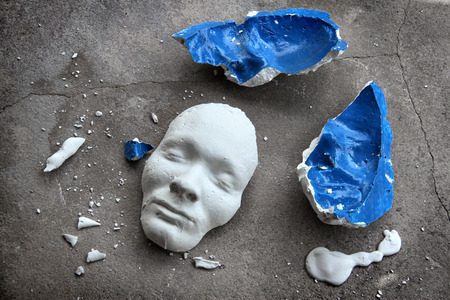 Plaster face mask between pieces of broken matt Stock fotó - 36970376