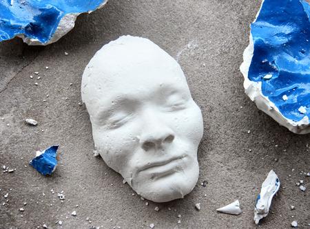 matt: Plaster face mask in the middle of pieces of broken matt