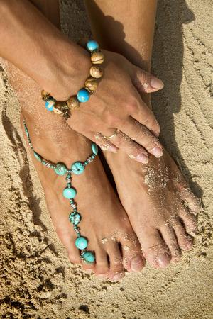 Woman posing with bracelets on beach sand