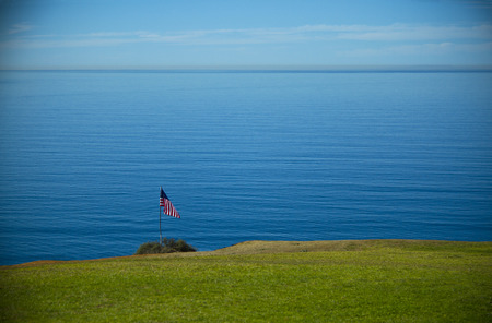 american banner in front of endless expance of pacific ocean photo