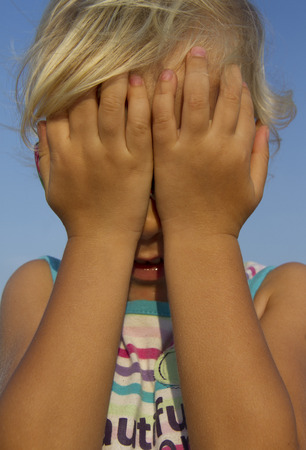 secrete: little girl hiding behind her hands