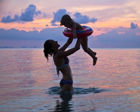 mama and baby playing in the water against the sunset Stock Photo