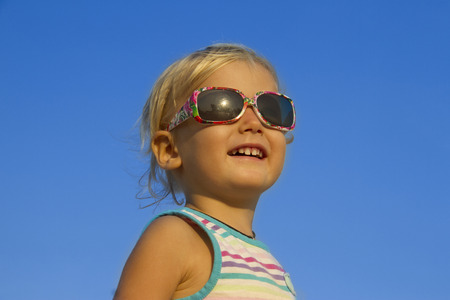potrait of a cute smiling little girl in sunglasses photo