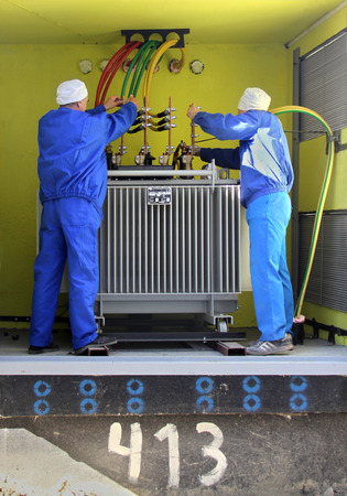electricians working at high voltage power transformer