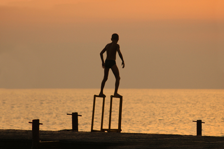 pierce: silouette of a boy ready to dive from pierce in front of brightly lighted sea Stock Photo