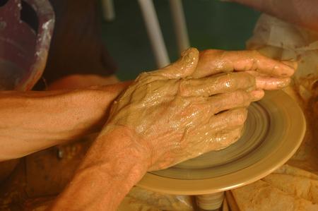 alfarero: Las manos del maestro en la rueda de alfarero Foto de archivo