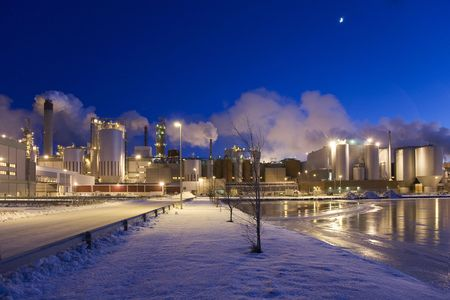 Paper mill on a winter night immediately after sunset, when sky has turned blue.