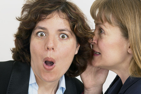 two business women whisper a secret in close up of ear and mouth