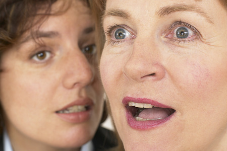 two business women whisper a secret in close up of ear and mouth photo
