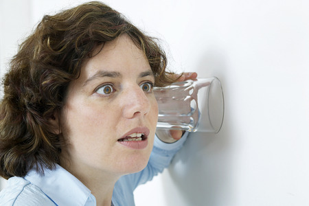 snoop: woman listening to conversation through wall with an ear to a glass