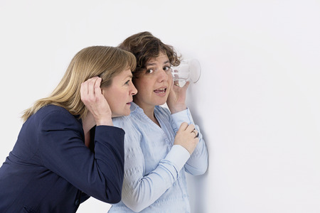 furtive: Two business women listening to a conversation through a wall with an ear to a glass