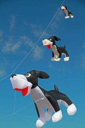 Dog shaped kites against clear blue sky