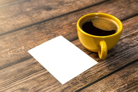 Yellow cup of hot coffee with notepaper  background wood ,close up.